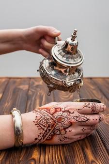 Persona con mehndi vertiendo té en taza