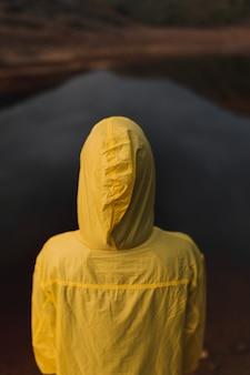 Una persona mirando hacia la cámara con una sudadera amarilla de piel oleosa mirando un río rojo en españa.