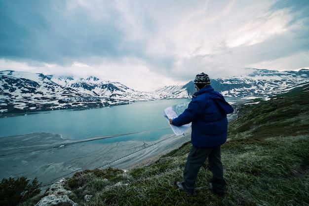 Una persona mirando el mapa de trekking, cielo dramático al atardecer, lago y montañas nevadas, sensación de frío nórdico