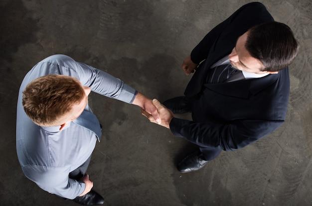 Persona de negocios de apretón de manos en concepto de oficina de trabajo en equipo y asociación