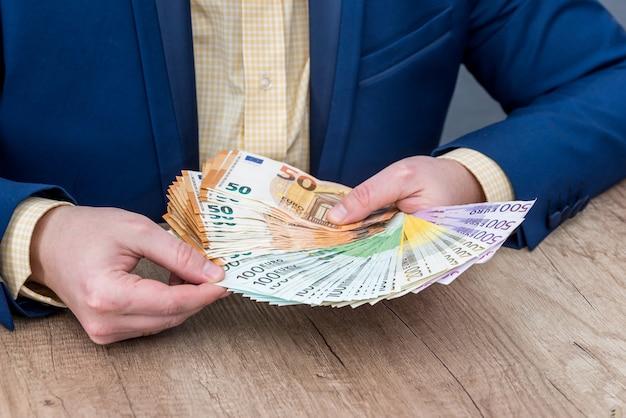 Persona de negocios colocando billetes en euros en el ventilador