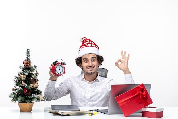 Persona de negocios joven con sombrero de santa claus y mostrando reloj y haciendo gesto de anteojos sentado en la oficina sobre fondo blanco