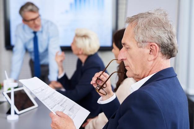 Persona de negocios leyendo documentos importantes