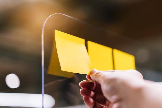 Persona de negocios con nota adhesiva en el separador de plexiglás