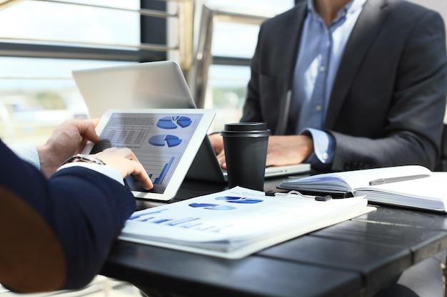 Persona de negocios que analiza las estadísticas financieras que se muestran en la pantalla de la tableta