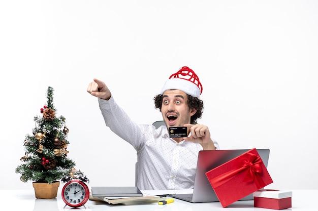 Persona de negocios con sombrero de santa claus y sosteniendo su tarjeta bancaria mirando y apuntando algo con sorpresa en la oficina