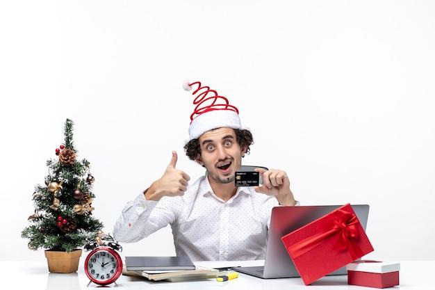 Persona de negocios con sombrero de santa claus y sosteniendo su tarjeta bancaria mirando y haciendo un gesto de ok en la oficina