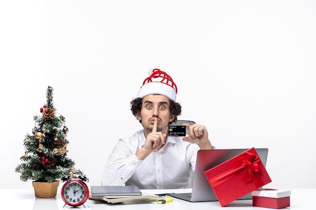 Persona de negocios con sombrero de santa claus y sosteniendo su tarjeta bancaria mirando con sorpresa haciendo gesto de silencio en la oficina
