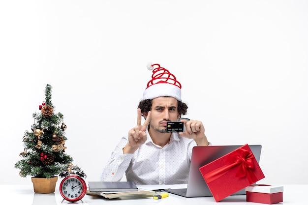 Persona de negocios con sombrero de santa claus y sosteniendo su tarjeta bancaria mirando con sorpresa en la oficina