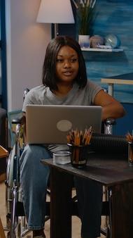 Persona negra no válida con computadora portátil diseñando obras de arte en un espacio creativo en casa. artística mujer afroamericana en silla de ruedas trabajando con dispositivo en busca de inspiración para obra maestra