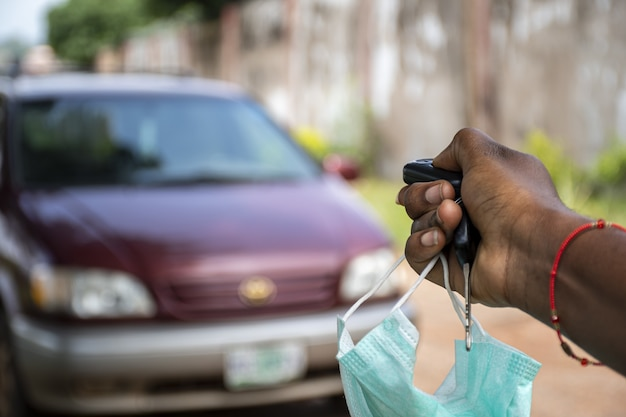 Persona negra que usa el control remoto de un automóvil para desbloquear un automóvil, sosteniendo una máscara facial