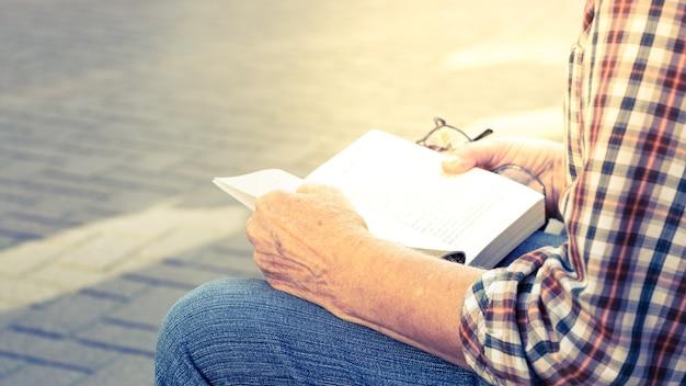 Persona no identificada con camisa a rayas y jeans azul leyendo un libro en la calle arbat, esperando a que aparezcan amigos, moscú, rusia (tono vintage y agregando luz cálida)