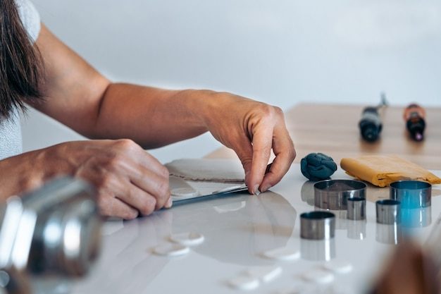Persona no reconocida que crea coloridas joyas hechas a mano en casa con arcilla.