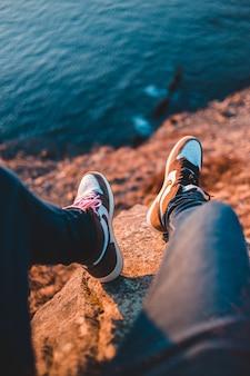 Persona en pantalones negros y zapatillas marrones y blancas sentada sobre una roca marrón cerca del cuerpo de cerca cerca cerca