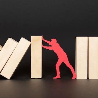 Persona de papel rojo luchando sosteniendo piezas de madera