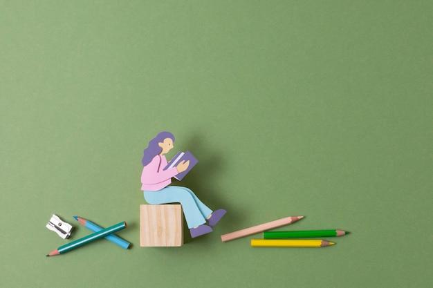 Persona de papel vista superior con crayones