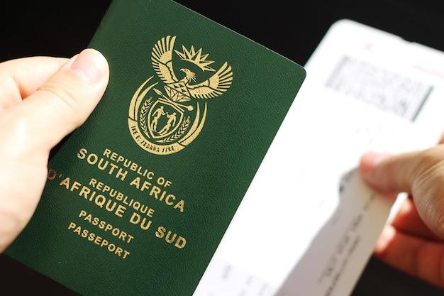 Persona con pasaporte de la república de sudáfrica y billete de avión