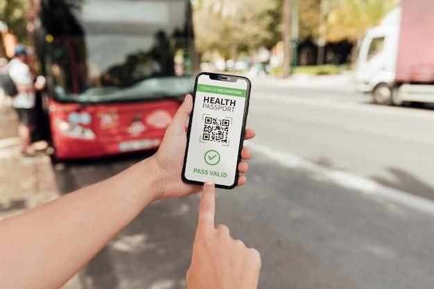 Persona con pasaporte de salud virtual en el teléfono inteligente en la estación de autobuses