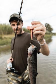 Persona pescando un pez con una caña de pescar