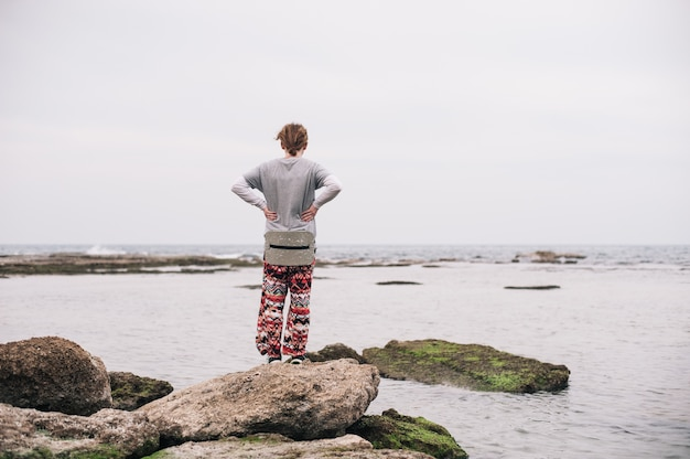 Persona de pie sobre las rocas cubiertas de musgo en el cuerpo del agua