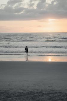 Persona de pie solo en la orilla de una playa con el reflejo de un sol poniente
