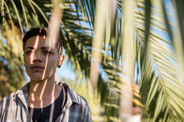 Persona de pie a la sombra de las ramas de palmera.