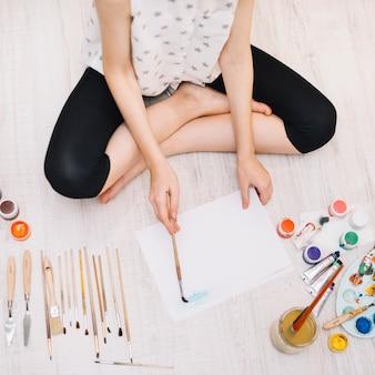 Persona pintando con acuarela en el piso.