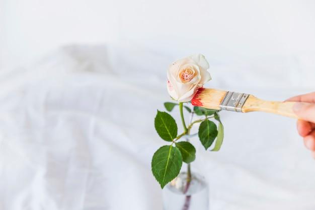 Persona pintando rosa con pincel sobre mesa blanca