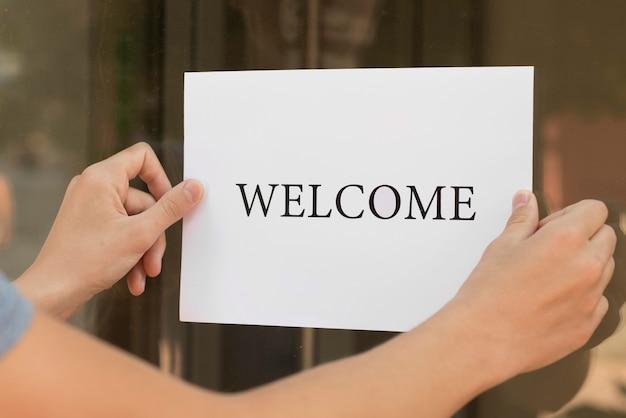 Persona poniendo un cartel de bienvenida en una puerta