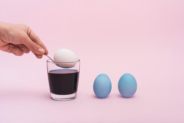 Persona poniendo cuchara con huevo en vaso con pintura