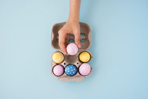 Persona poniendo huevo de pascua en caja