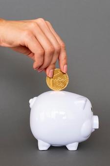 Persona poniendo monedas de hucha blanca