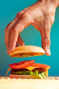 Persona de primer plano con bollo de hamburguesa y fondo azul