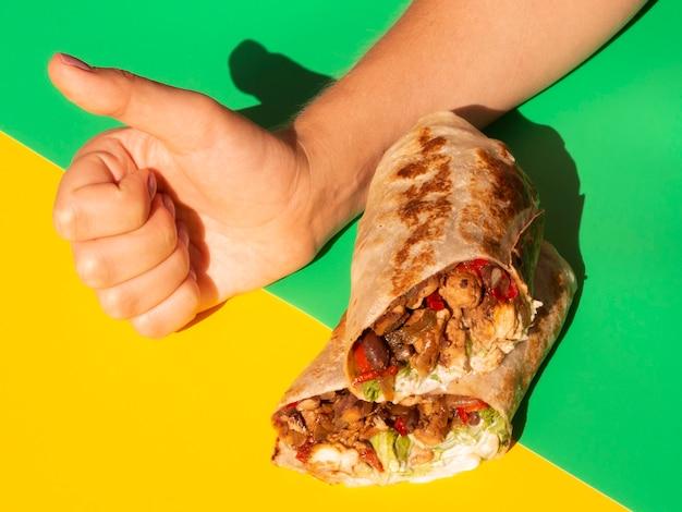 Persona de primer plano con burrito mostrando aprobación