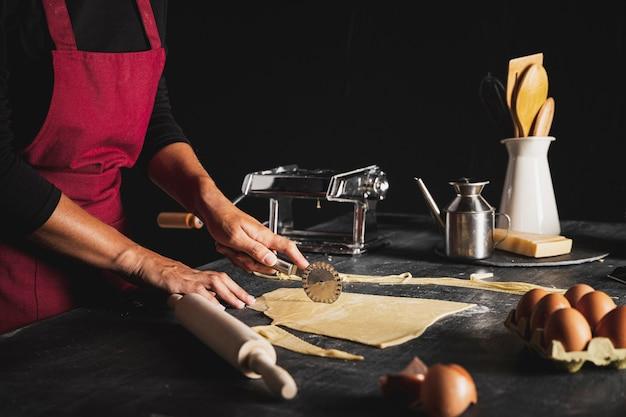Persona de primer plano con cortador de pizza y masa