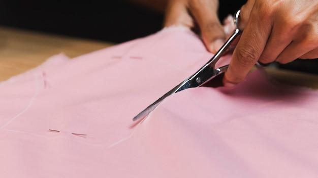 Persona de primer plano cortando un material de tela