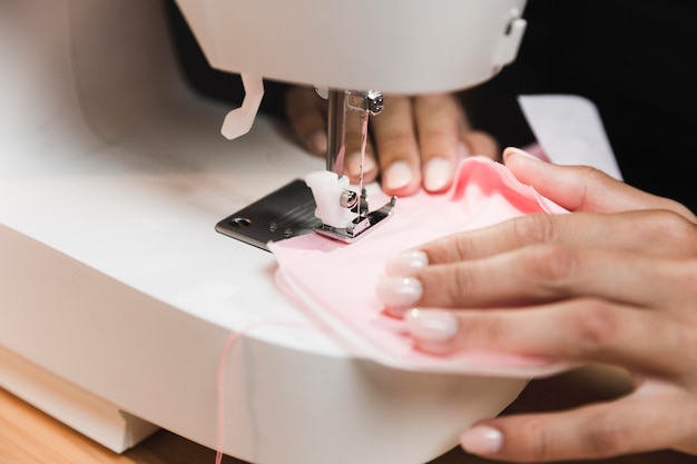 Persona de primer plano cosiendo una máscara médica con una máquina de coser
