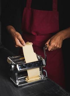 Persona de primer plano con delantal rojo haciendo pasta
