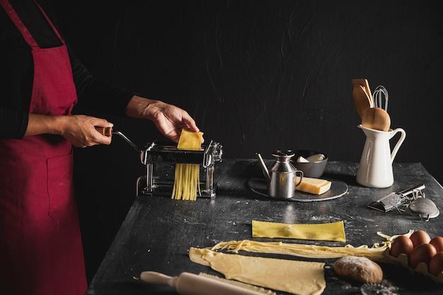 Persona de primer plano con delantal rojo y máquina de pasta