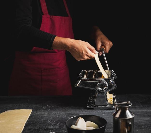 Persona de primer plano con delantal rojo y máquina de pastelería