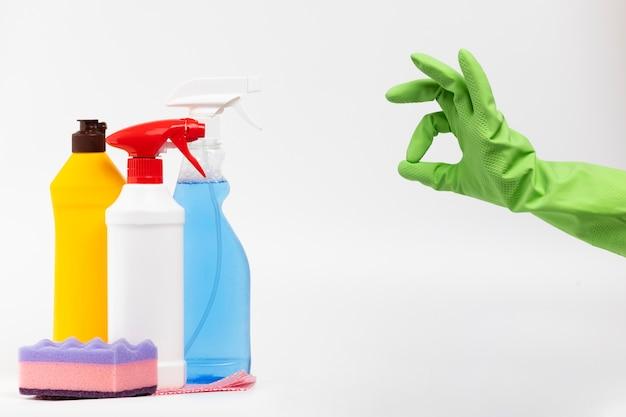 Persona de primer plano con guantes verdes y productos de limpieza