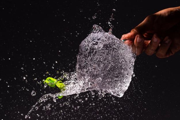 Persona de primer plano haciendo estallar un globo de agua