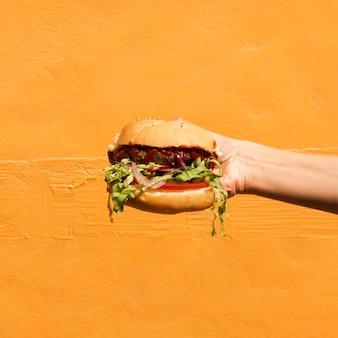 Persona de primer plano con hamburguesa y fondo naranja