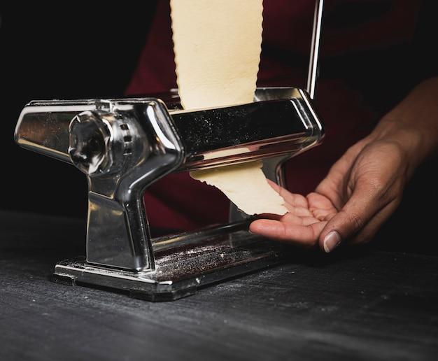 Persona de primer plano con máquina para pasta
