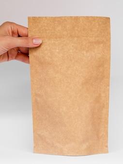 Persona de primer plano sosteniendo una bolsa de papel
