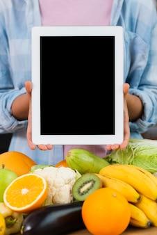 Persona de primer plano sosteniendo maqueta de tableta