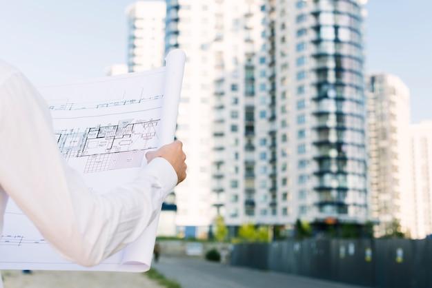 Persona de primer plano sosteniendo planes de construcción