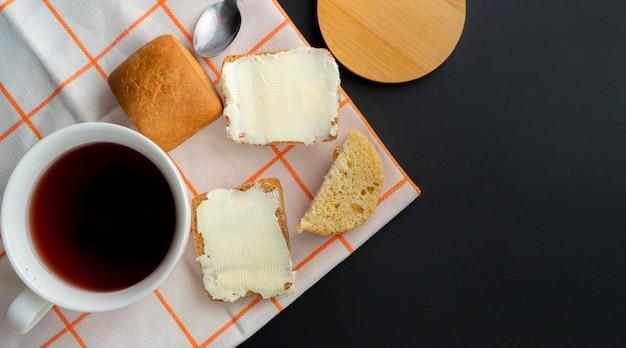 La persona puso un trozo de mantequilla en una rebanada de pan y una taza de café sobre la mesa, las comidas del desayuno