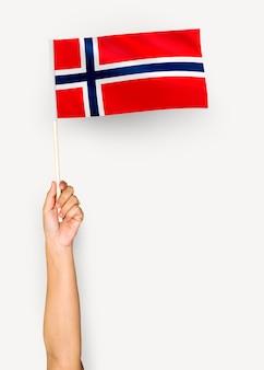 Persona que agita la bandera del reino de noruega