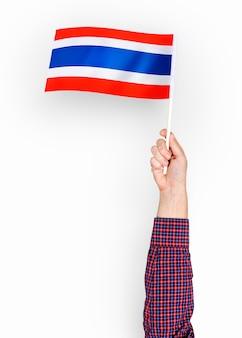 Persona que agita la bandera del reino de tailandia